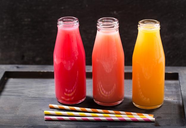 木製のテーブルの上の瓶の中の様々な冷たい飲み物