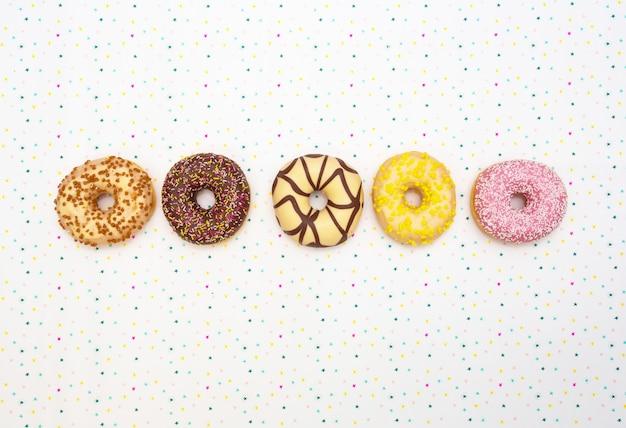 Различные цветные вкусные пончики. концепция праздника. вид сверху