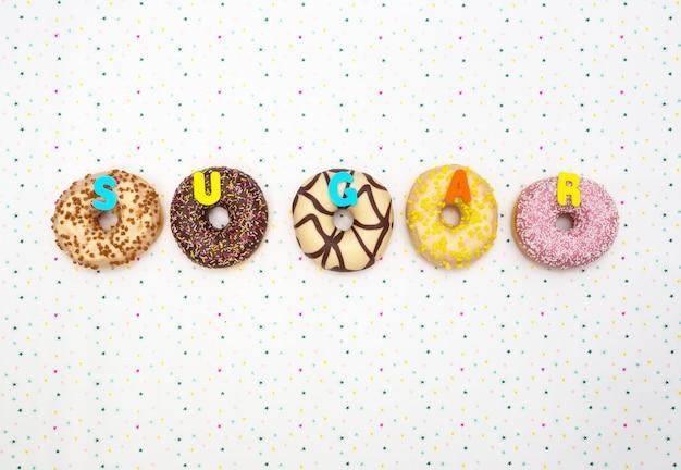 Различные цветные вкусные пончики со словом «сахар», концепция празднования. вид сверху