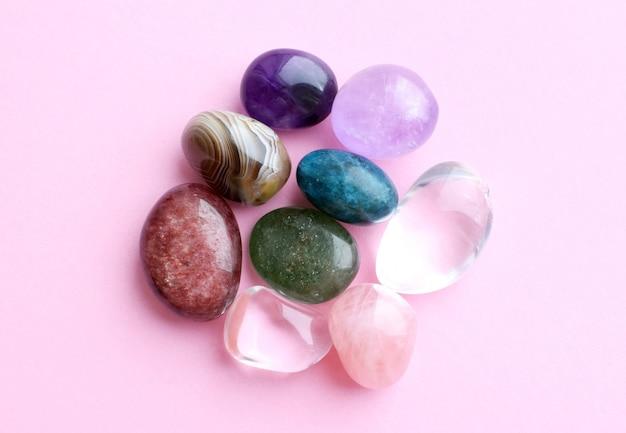 Драгоценные камни разного цвета, необработанные и обработанные. аметист, розовый кварц, агат, апатит, авантюрин на розовой стене.