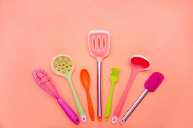 Various colored silicone kitchen utensils on coral background. copy space for your text