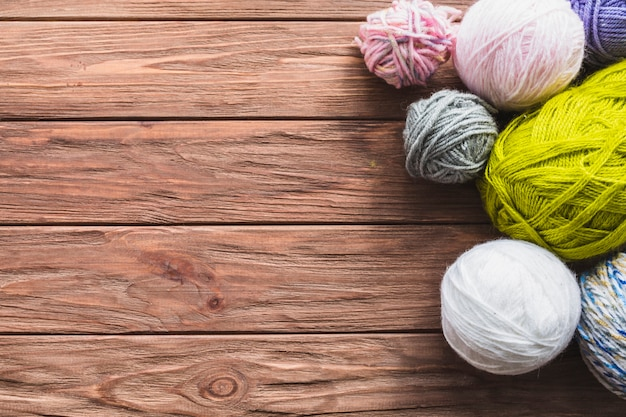 Various colorful ball of yarns on wooden background