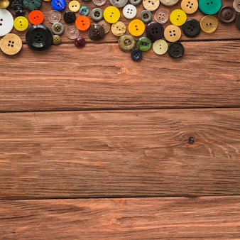 Various colorful buttons on wooden plank