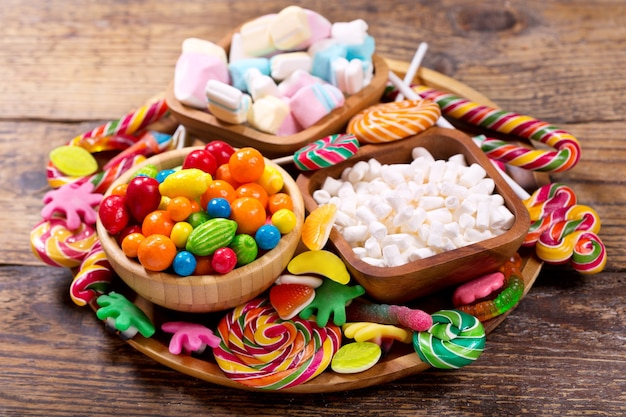 나무 테이블에 다양한 다채로운 사탕, 젤리, 막대 사탕, 마시맬로 및 마멀레이드