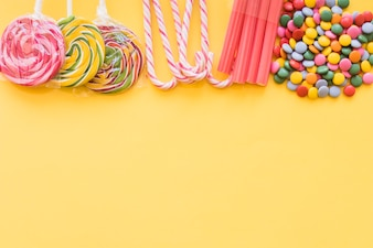 Various colorful candies on the yellow backdrop