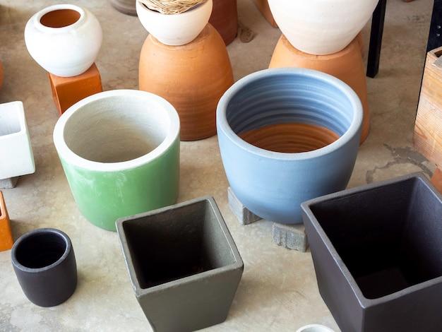콘크리트 바닥에 배열하는 다양한 다채로운 세라믹 화분. 빈 기하학적 세라믹 화분.