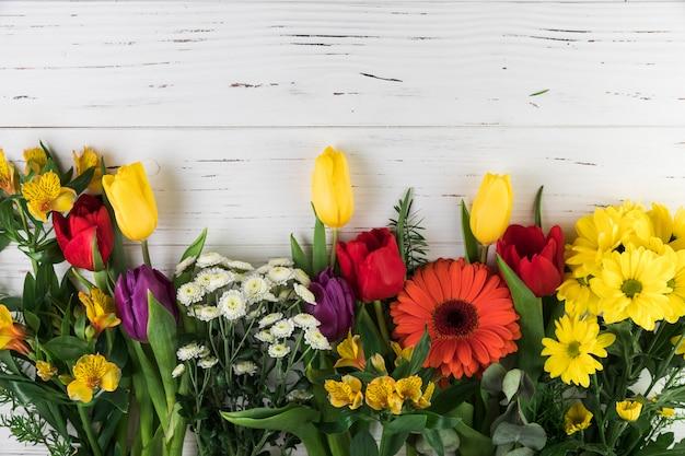 白い木製の背景に飾られた様々なカラフルな花の花束