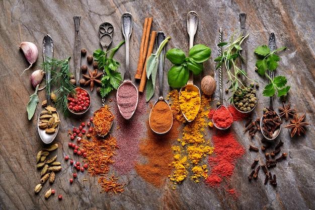 調理用スプーンのさまざまなカラフルなハーブとスパイス:ターメリック、ディル、パプリカ、シナモン、サフラン、バジル、ローズマリー。インドのスパイス。古い石の茶色の背景に。上面図。