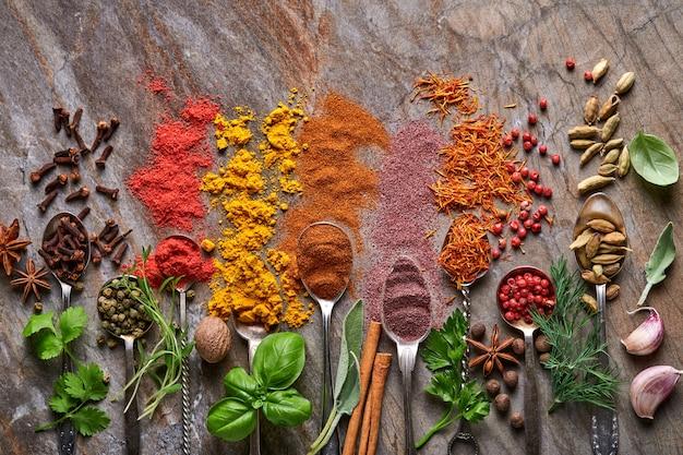 調理用スプーンのさまざまなカラフルなハーブとスパイス:ターメリック、ディル、パプリカ、シナモン、サフラン、バジル、ローズマリー。インドのスパイス。古い石の茶色の背景に。上面図