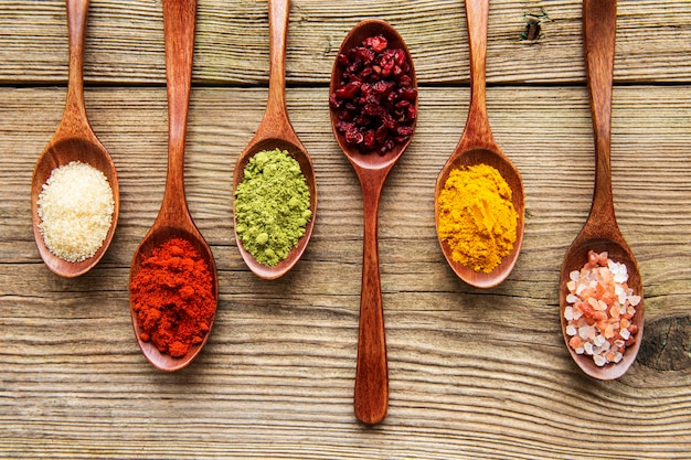 Various colorful herbs and spices on wooden table