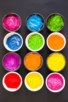 Various colorful holi color powder in the bowls on black background