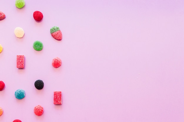 Various colorful jelly sugar candies on pink wallpaper