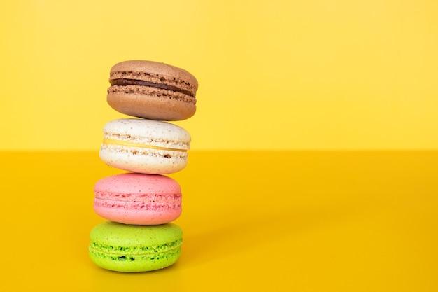Различные красочные миндальное печенье на желтой стене