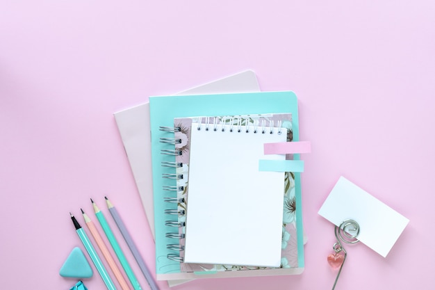 Various colorful stationery for school and office on pink background with copyspace.