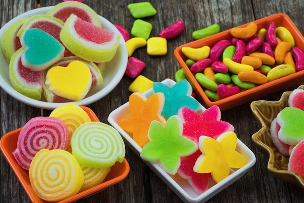 Various colorful sugary candy in container on old wooden plank