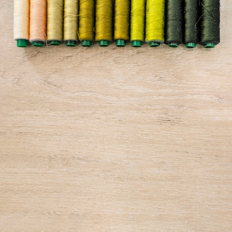 Various colorful threads arranged in a row on wooden background