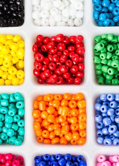 Various colors beads on the white plastic box close up