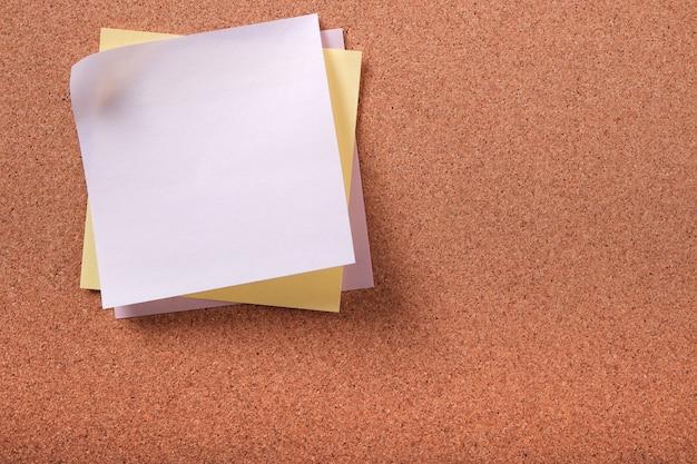 様々な色のコルクの背景にいくつかの粘着性のポストノート