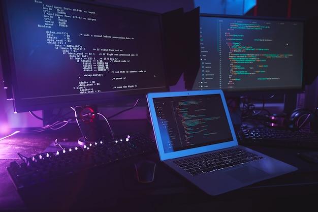 어두운 방, 사이버 보안 개념, 복사 공간에있는 테이블에 화면에 프로그래밍 코드가있는 다양한 컴퓨터 장비