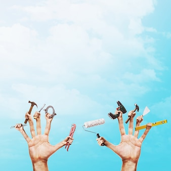Various construction tools in hands on a blue sky with copy space handyman concept