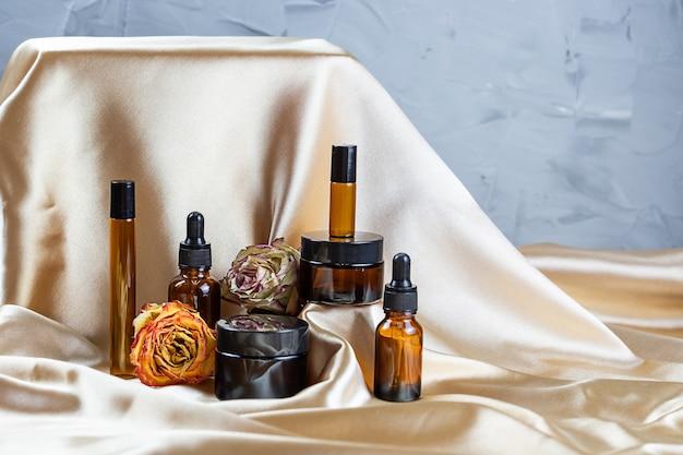 На складках шелковой атласной ткани в окружении засушенных цветов розы лежат различные емкости для хранения косметики из темного стекла. флакон духов, сыворотки или лосьона