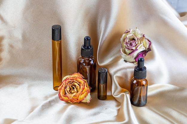 На складках шелковой атласной ткани в окружении засушенных цветов розы лежат различные емкости для хранения косметики из темного стекла. ароматизатор косметический косметический продукт.