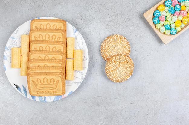 Различное печенье на тарелке с двумя печеньями рядом с конфетами на мраморном фоне. фото высокого качества
