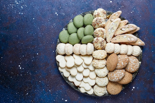 Various cookies in a wooden tray on gray background
