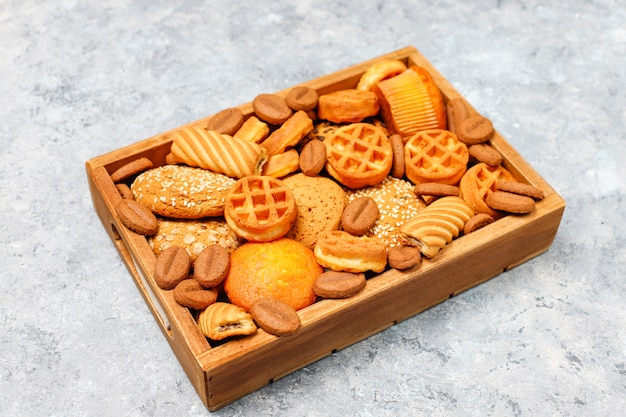 Various cookies in a wooden tray on gray surface