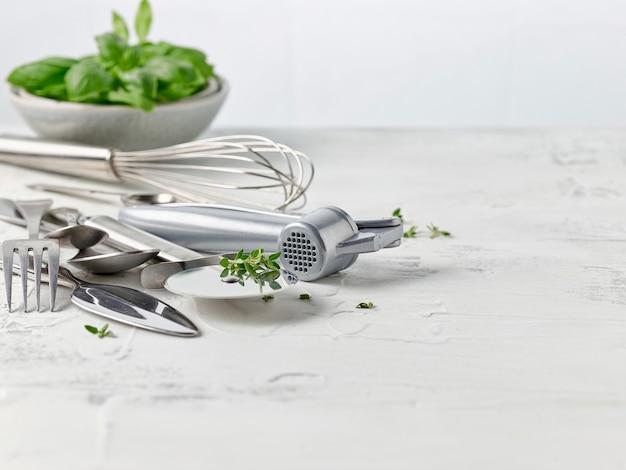 Различные кухонные принадлежности на белом кухонном столе