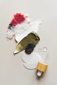 베이지색 배경에 다양한 화장품 마스크, 크림, 혈청, 스크럽, 로션 얼룩이 있습니다. 아름다움 질감입니다. 화장품 샘플입니다.