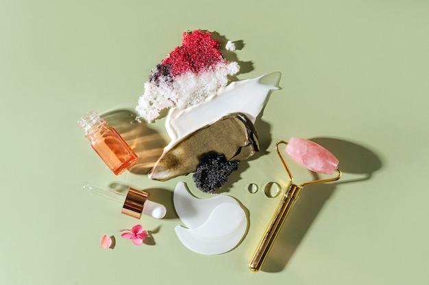 다양한 화장품 마스크, 크림, 혈청, 스크럽, 로션이 녹색 배경에 묻어 있습니다. 아름다움 질감입니다. 화장품 샘플입니다.