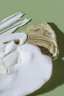 Various cosmetic mask, creams, serum, scrub and lotion smear on a green background. beauty texture. sample of a cosmetic product.