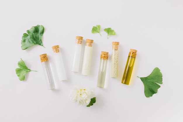 Various cosmetic products in test tube with gingko leaf and flower on white backdrop