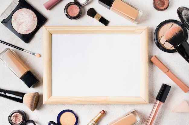 Various cosmetics and blank frame scattered on light background