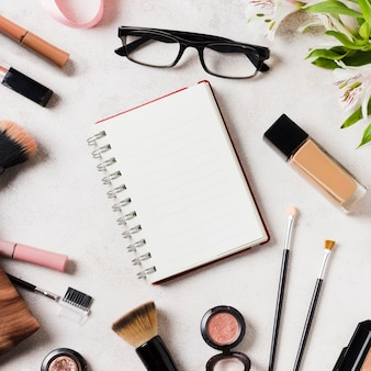 Various cosmetics and glasses scattered around blank notebook