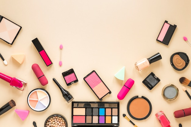 Various cosmetics scattered on beige table