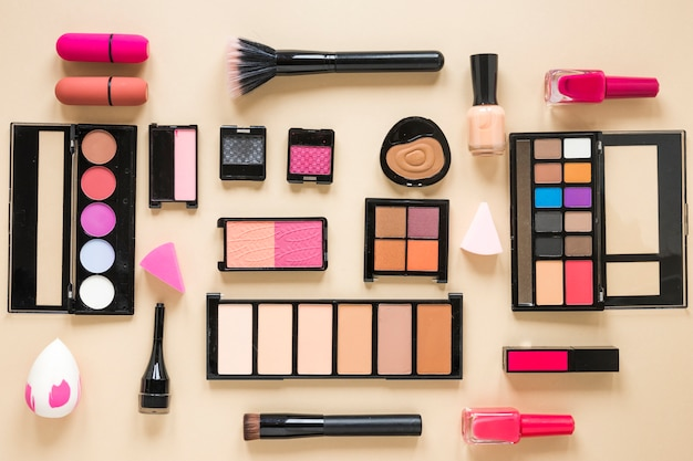 Various cosmetics types scattered on beige table