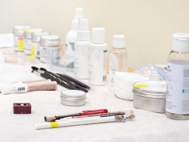 Various creams and eyebrow coloring products are on the table in the beauty salon, soft focus.