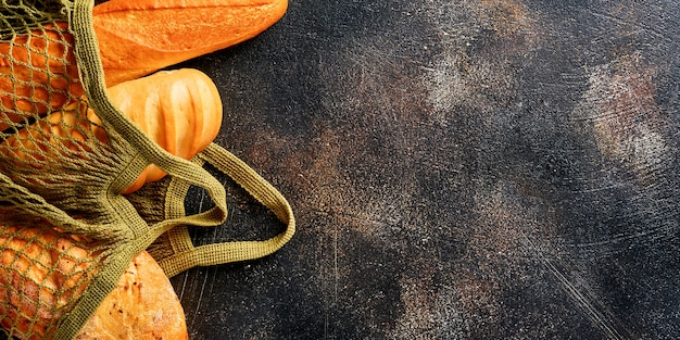 メッシュバッグまたはショッピングバッグのさまざまなサクサクのパンやパン、小麦粉、茶色の古いコンクリートの背景のテーブルの耳。上面図。バナー。
