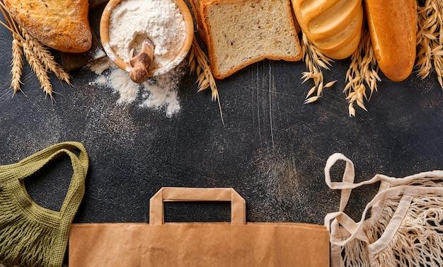 茶色の古いコンクリートの背景のテーブルにさまざまなサクサクのパンとパン、小麦粉、耳と紙袋、メッシュバッグまたはショッピングバッグ