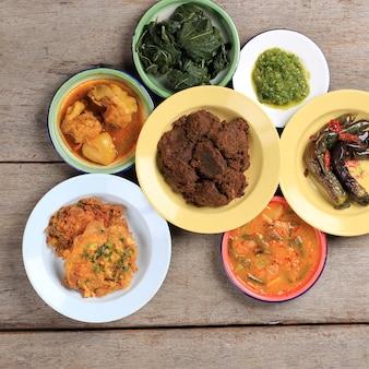 マサカンパダンまたはパダン料理と呼ばれるパダンのさまざまな料理。インドネシアで人気のある料理は、西スマトラのミナンから生まれ、素朴な背景に積み重ねられたプレートの層で提供されます