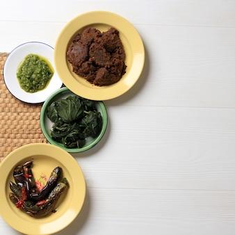 マサカンパダンまたはパダン料理と呼ばれるパダンのさまざまな料理。インドネシアで人気のある料理は、西スマトラのミナンから、白い背景の上の積み重ねられたプレートの層で提供されます