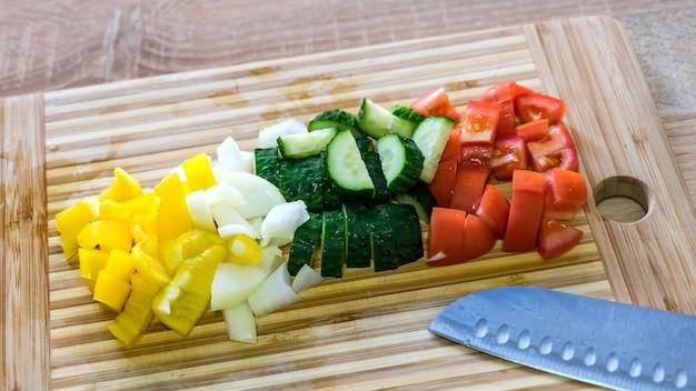 木の上の様々なカット野菜。ピーマン、玉ねぎ、きゅうり、トマト。ベジ