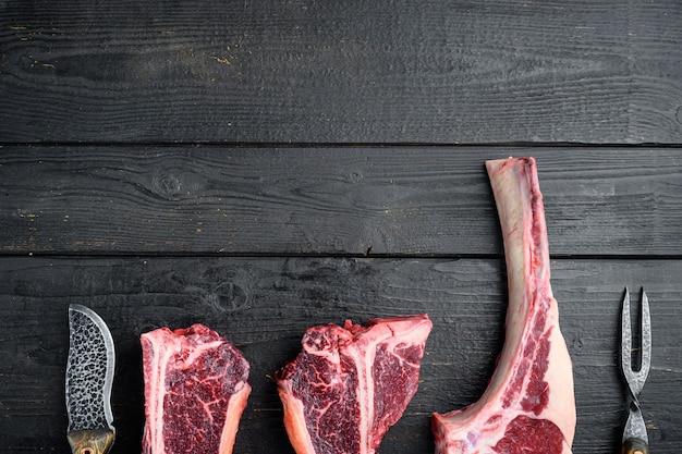 Различные куски мяса сухой выдержанной говядины, томагавк, т-кость или портерхаус и клубный стейк на черном деревянном столе