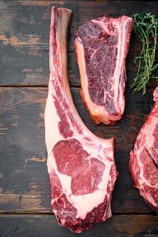 Различные куски мяса, набор из сухой выдержанной говядины, томагавк, кость или портерхаус и клубный стейк, на фоне старого темного деревянного стола, плоская планировка, вид сверху, с местом для текста