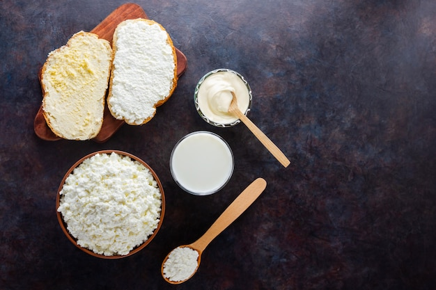 Various dairy products. bread with cream cheese on a black table. top view