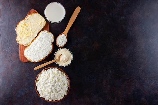 Various dairy products. milk, cottage cheese and sour cream on a dark table