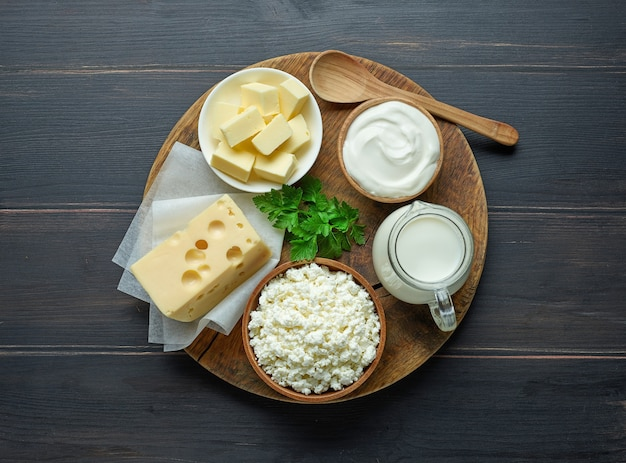 Various dairy products on wooden kitchen table, top view