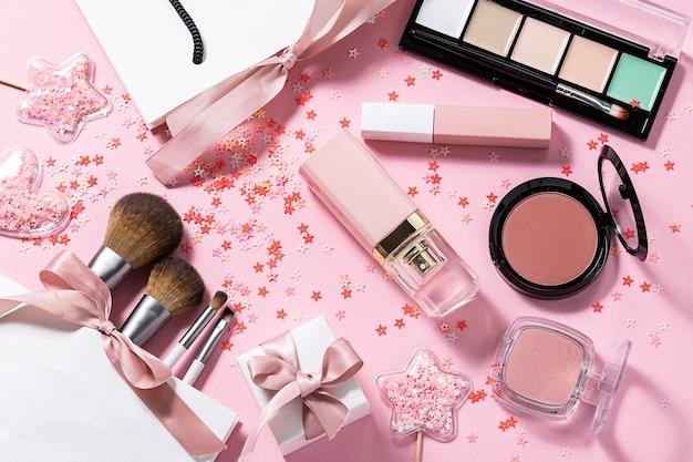 Различная декоративная косметика, парфюмерия, кисти для макияжа и подарочные коробки и блестящие украшения на розовом пастельном столе.